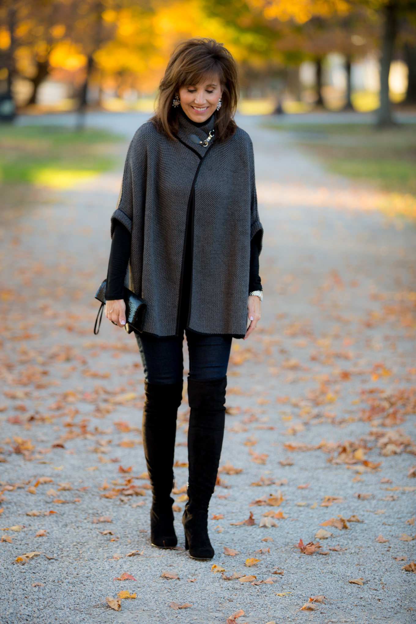 Fashion blogger, Cyndi Spivey, styles a classic poncho with over the knee boots.