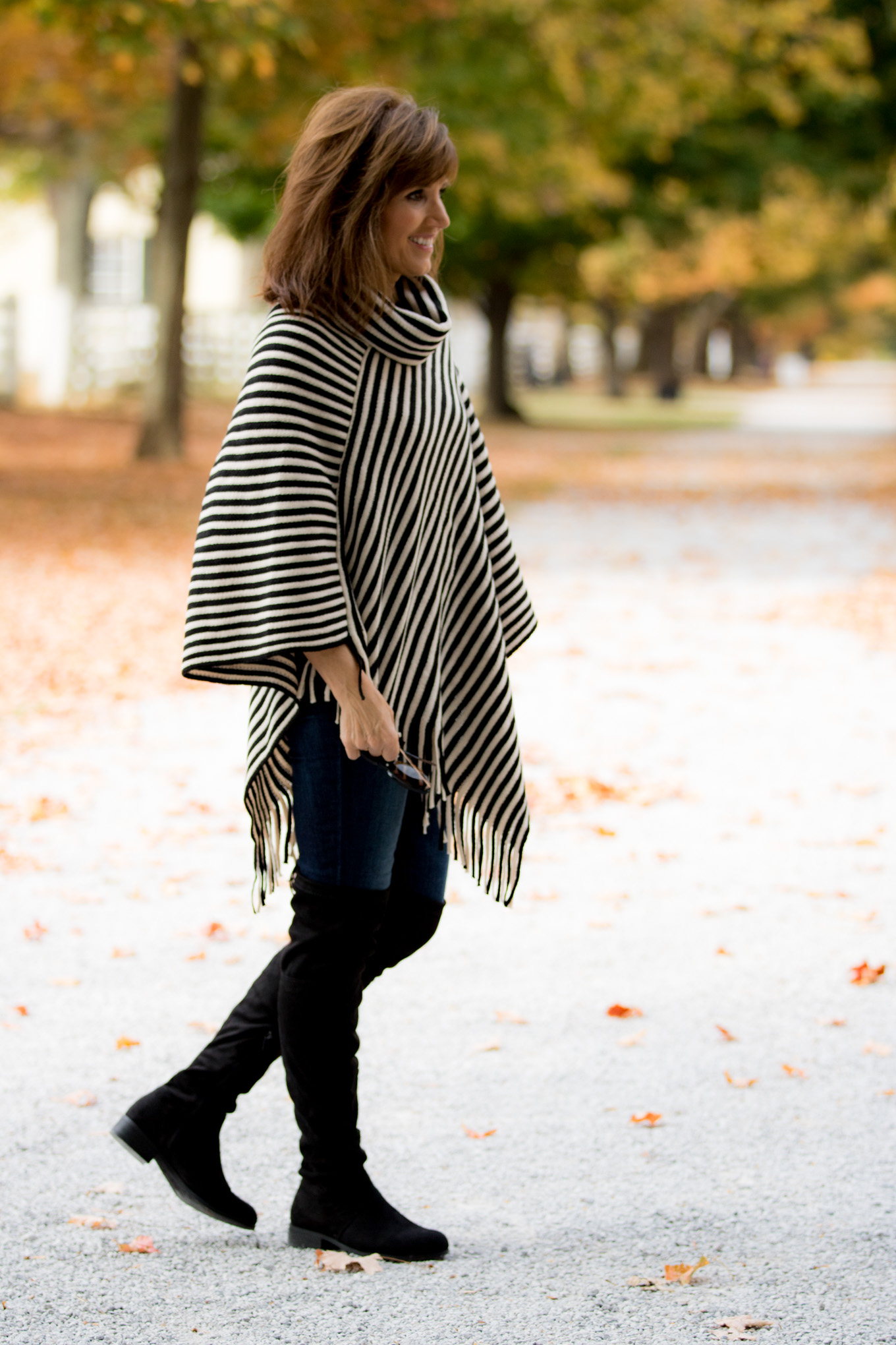 Fashion blogger, Cyndi Spivey, styling a striped poncho from Glamour Farms Boutique.