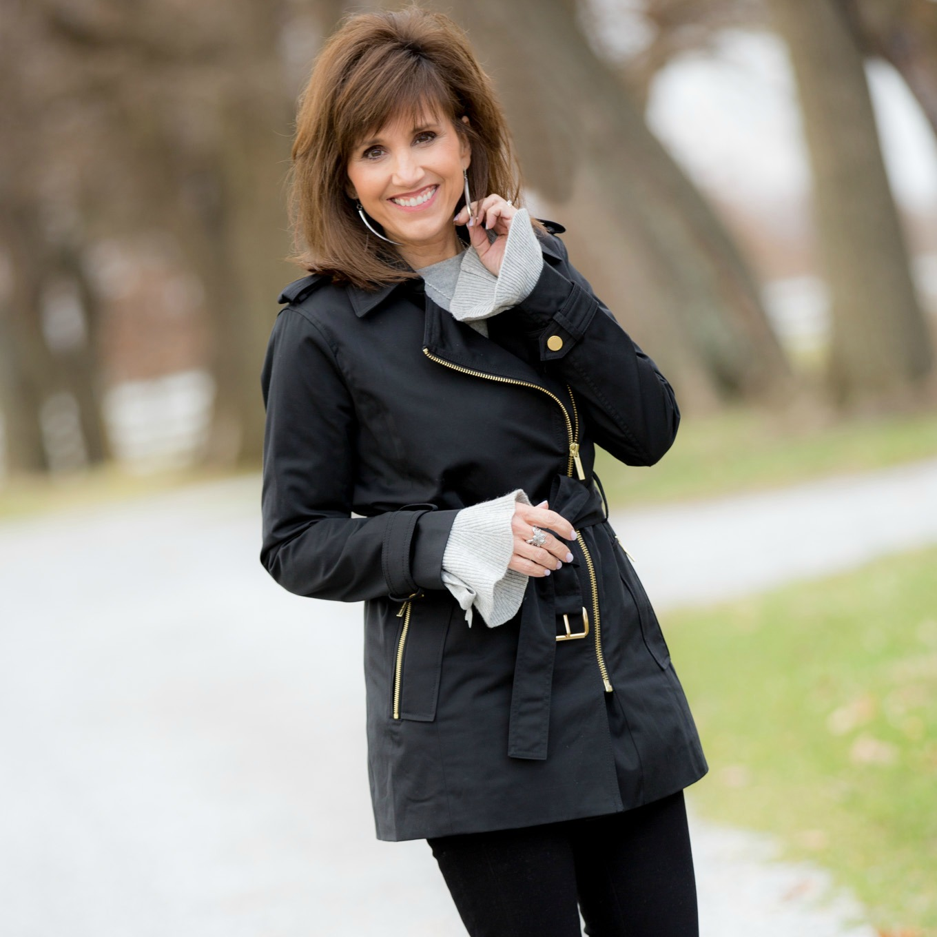 Fashion blogger, Cyndi Spivey, styling a black trench coat from Macy's.