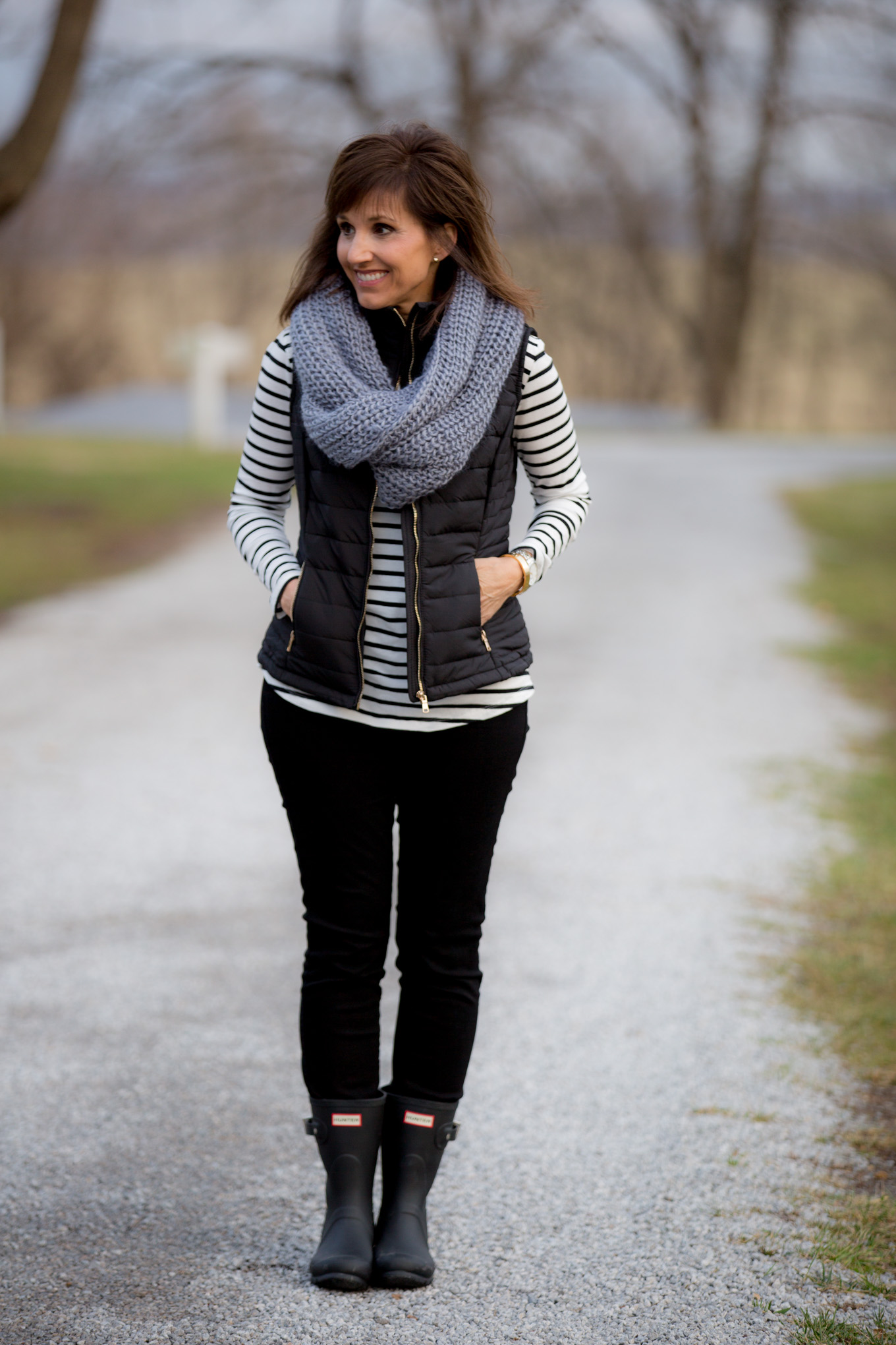 Over 40 fashion blogger, Cyndi Spivey, styling a black quilted vest.