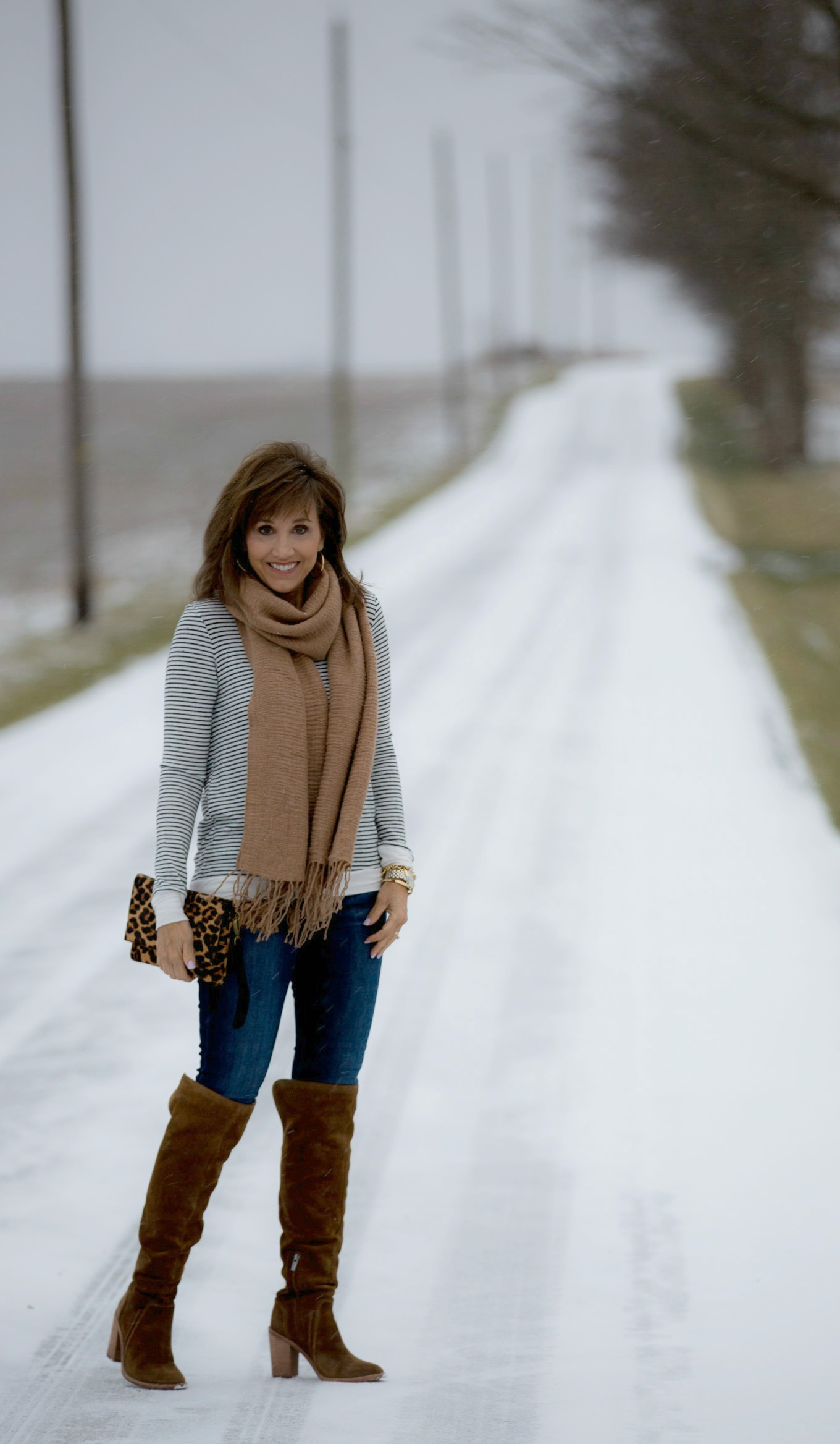 Fashion blogger, Cyndi Spivey, styling a striped top and fringe scarf.